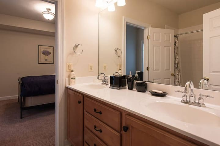 Full bathroom next to guest bedroom on lower level with tub and shower and two sinks