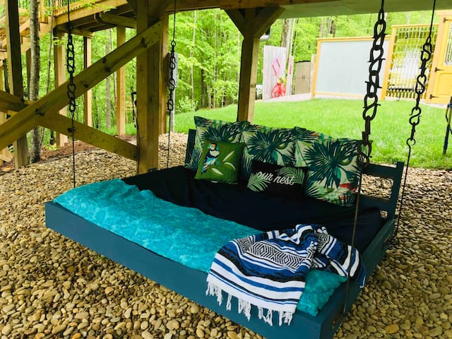 Underneath the treehouse is the bed swing! It is full size and custom built by my husband with a piece of vintage wrought iron column from your grandma's porch! The chains were  hand forged by a local ironsmith.