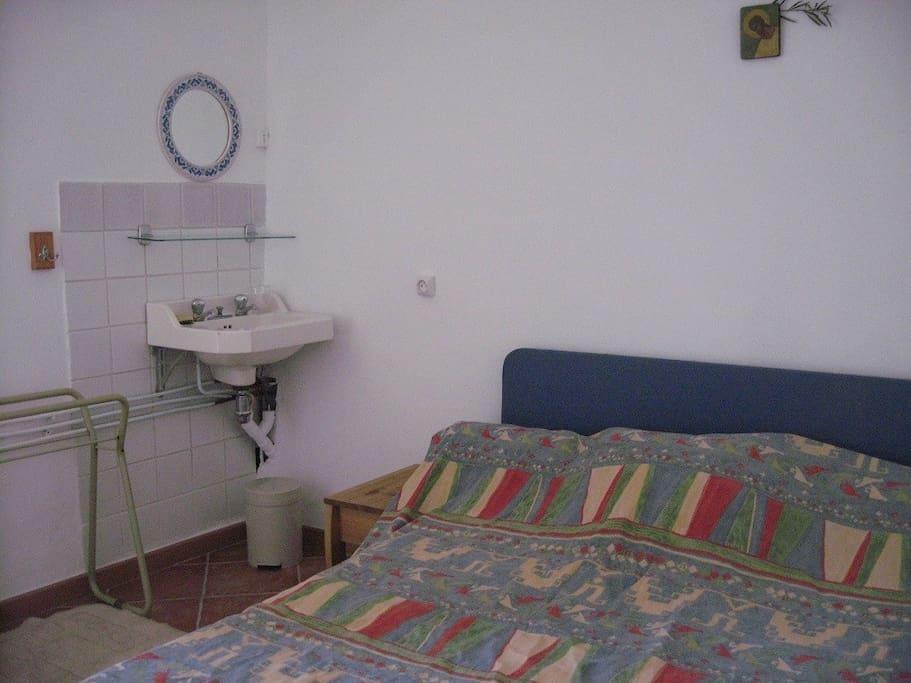 Chambre avec lit double et lavabo
