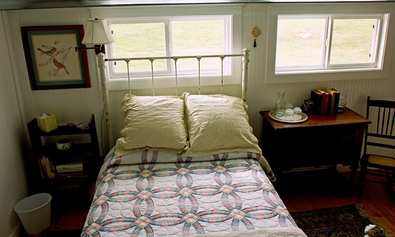 Double bed in loft, windows look out over pasture