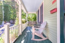 Front porch with hanging swing, rocking chair, deck furniture, and flourishing gardens and flowers galore!