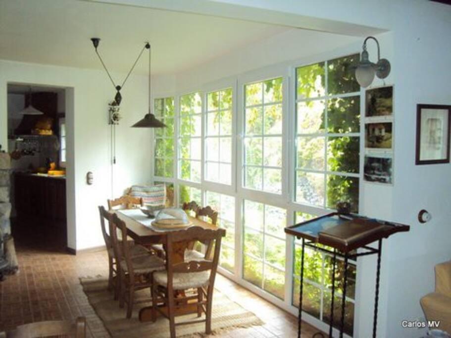 Sala de jantar com cozinha ao fundo.