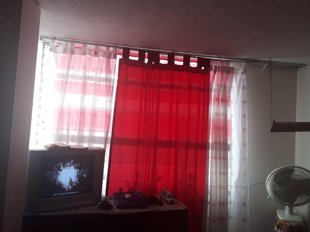Habitación con cama doble, mueble multiusos y televisor.