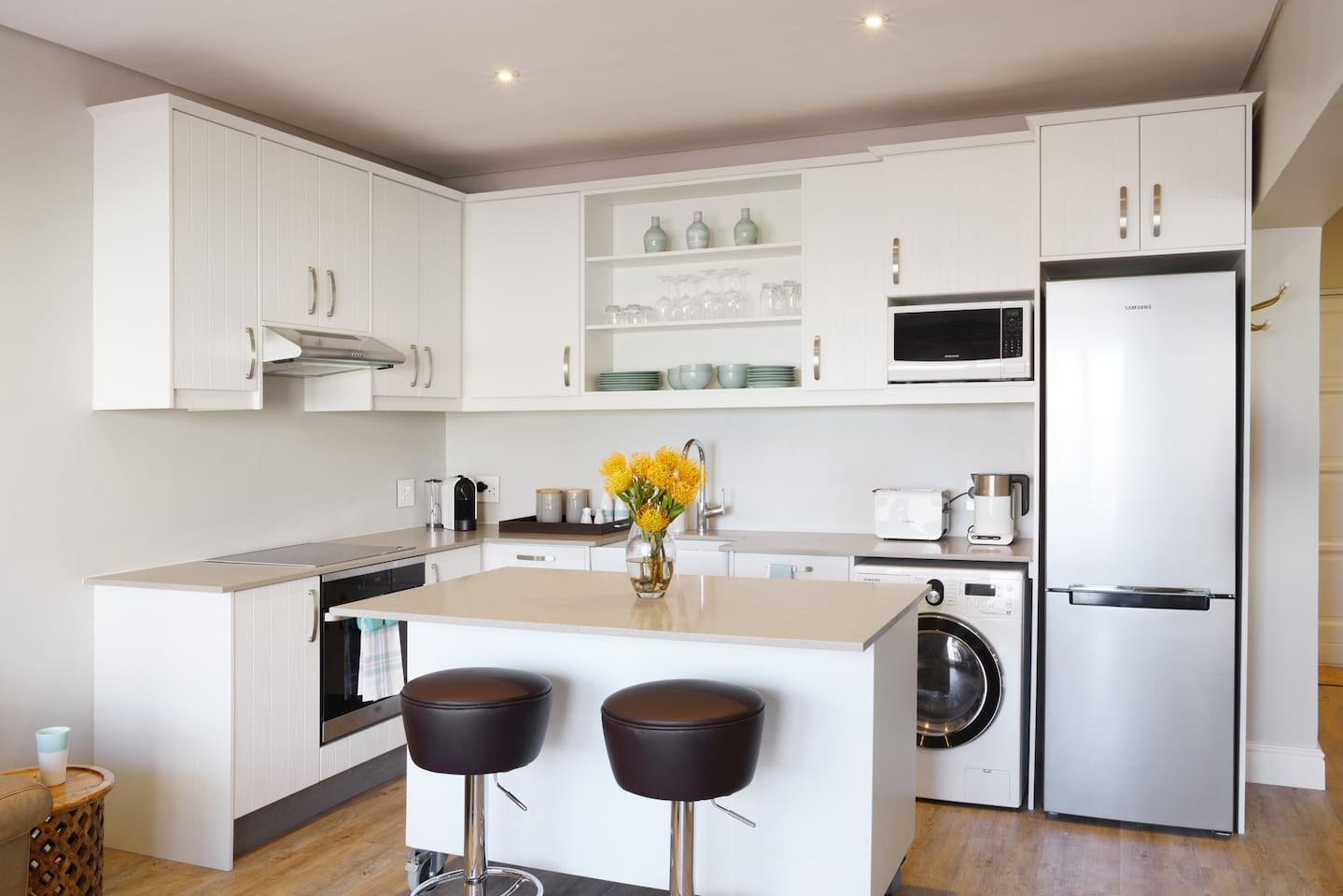 Kitchen area with island, equipped with touch oven, hob, extractor, microwave, washer dryer and full size fridge freezer