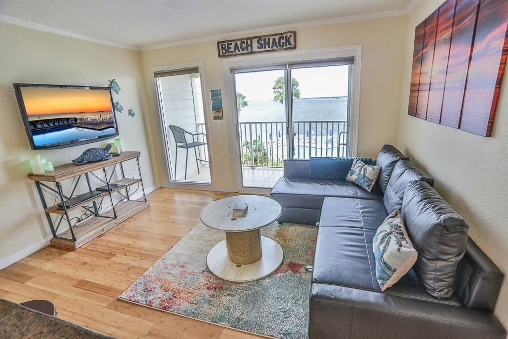 Relax in the newly decorated living room with private balcony.   Sofa converts to queen bed with linens stored under chaise part.