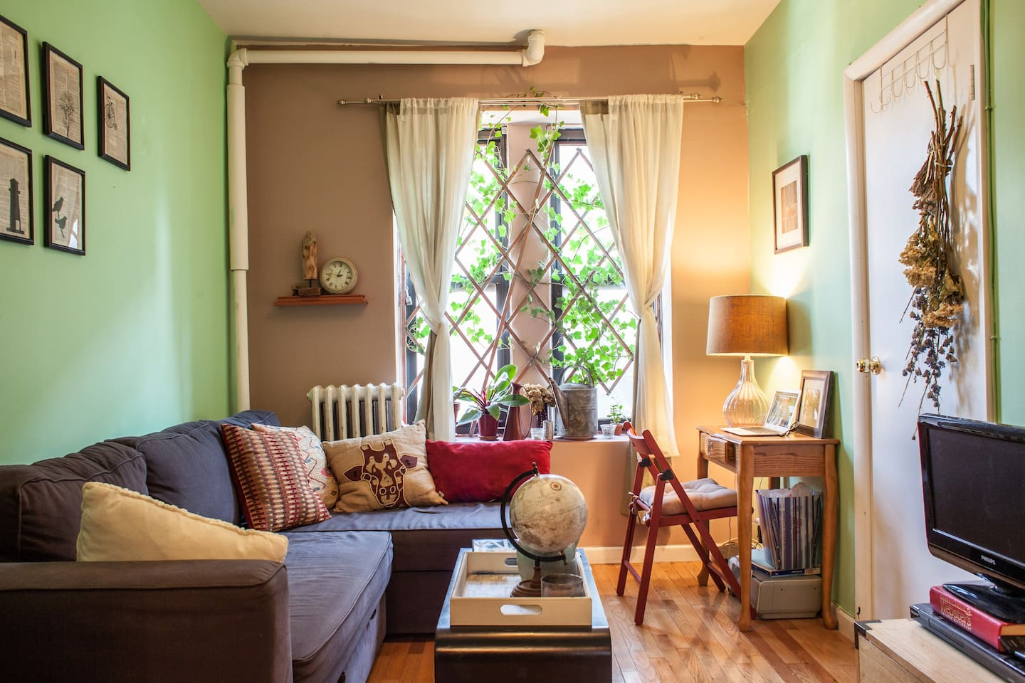 Cozy living room with Satellite TV (no cable),  DVD player, couch that converts to a full bed, and window garden.