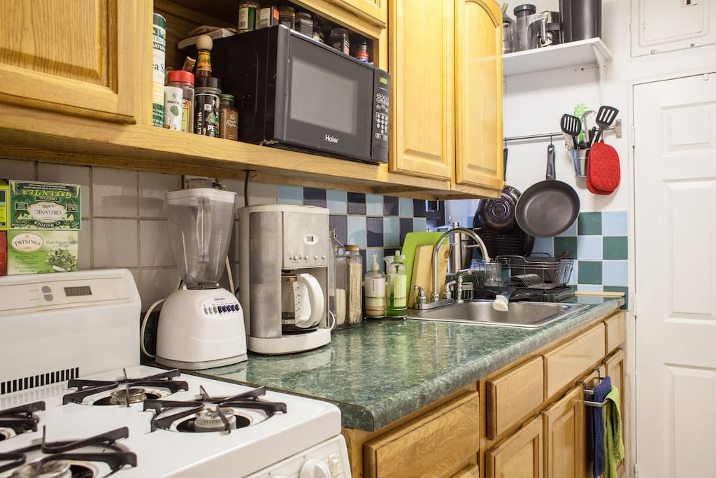 Kitchen with coffee maker, microwave, croc pot, juicer, and blender.