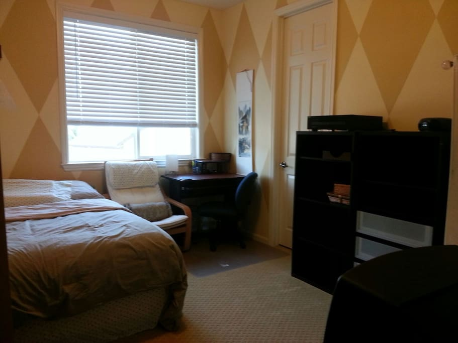 Wide view of the room with beige sheet set.