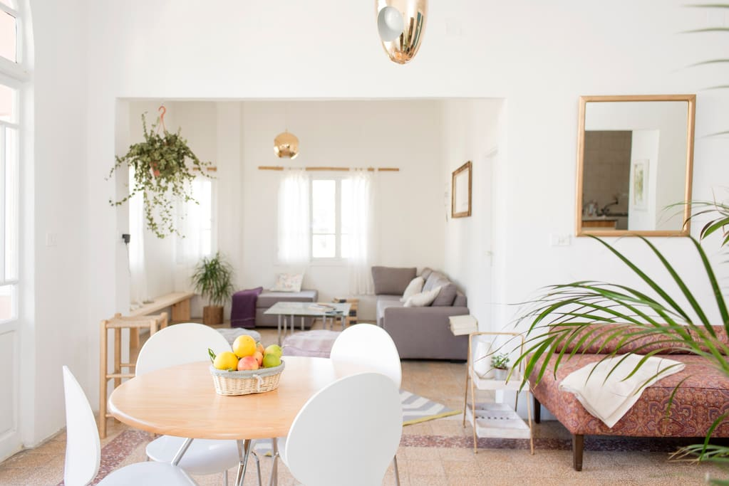 Two separate living areas divided by a cozy dining table help create even more space to this already spacious apartment.