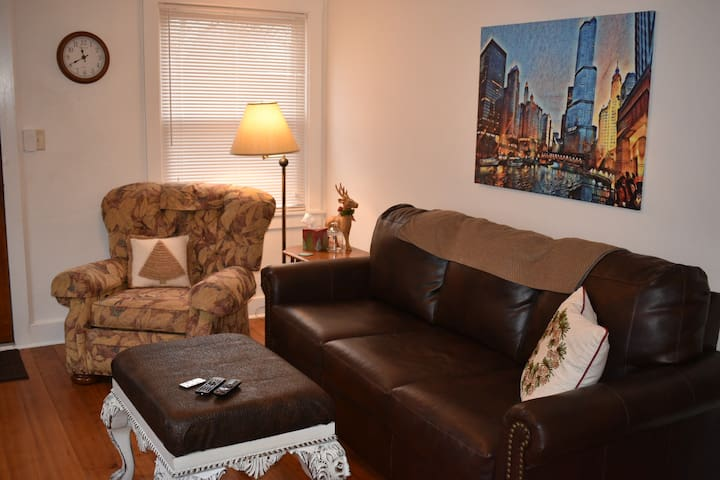 A comfortable living room with a Queen sofa sleeper, foot stool, over sized chair and original artwork of the Chicago River make this your home away from home!