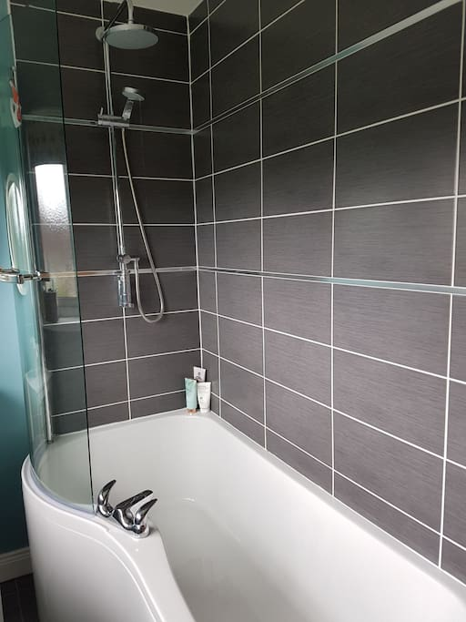 Contemporary shared bathroom with lock on door. Modern bath with multi shower heads. Instant hot water.