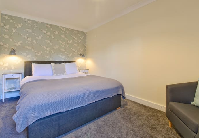 Bedroom with king sized bed and ensuite bathroom.