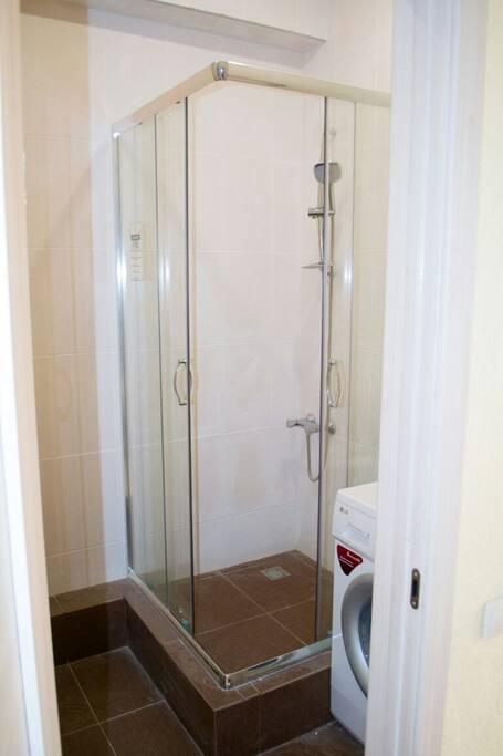В туалете душевая кабина, унитаз, раковина и стиральная машина
