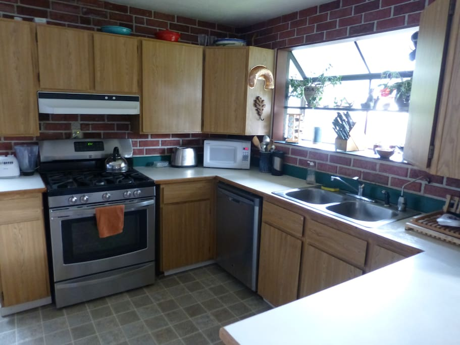 Kitchen includes gas  stove, large fridge, and dishwasher.