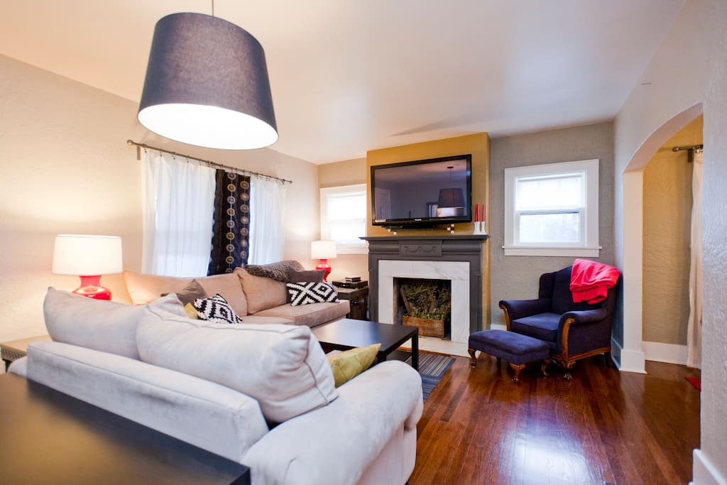 Cozy living room with sleeper sofa, original fireplace, stucco walls, and hardwoods throughout!