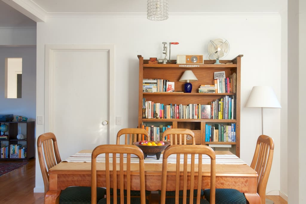 Dining area in the open plan downstairs living space has a beatifully restored 1930s table and vintage side-board with plenty of books.