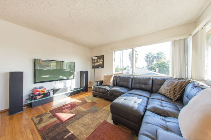 Living room with leather sofa and 60 inch flat panel television.