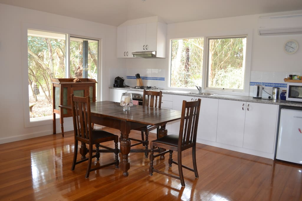 Fully equipped kitchen with oven, microwave, fridge, double sink, coffee machine, and dining room table.