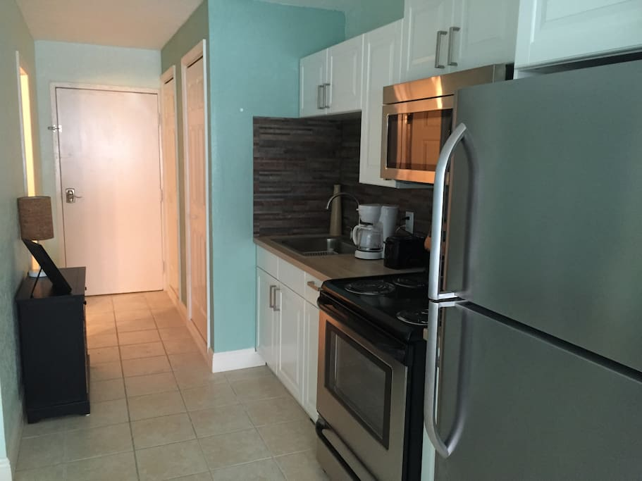New kitchen appliances with utensils, plates, toaster, coffee maker included.