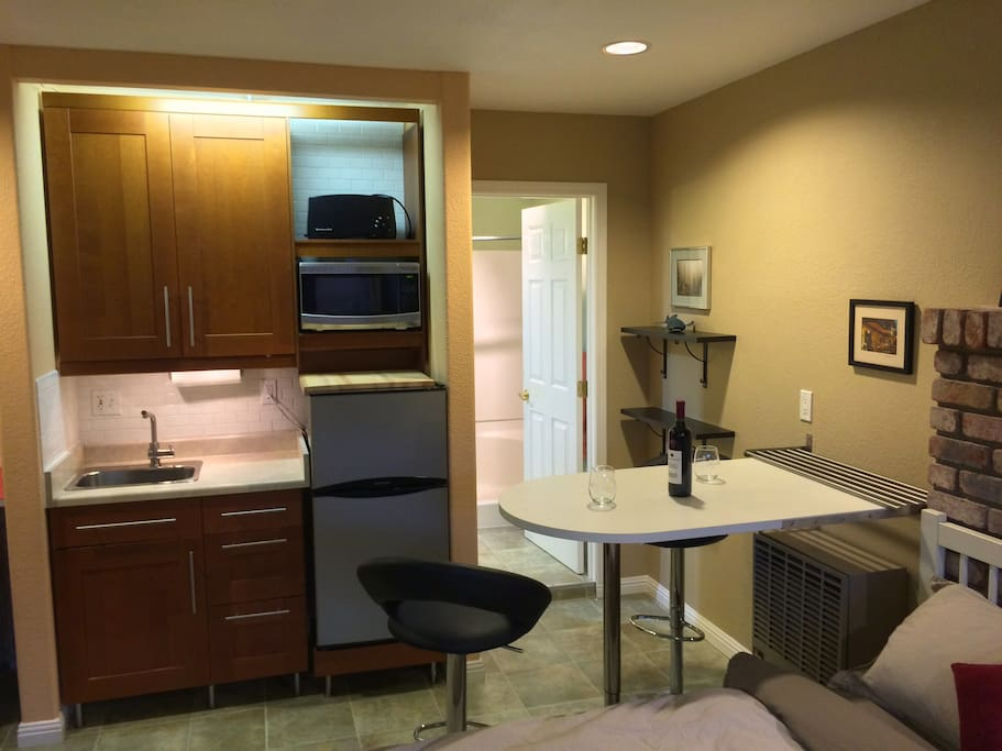The kitchenette, dining area, Microwave, Toaster, Fridge, deep basin sink.