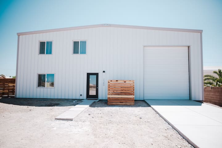 This amazing modern industrial home is inside a 3,000 square foot shop allowing guests to securely park all their favorite toys inside the 60' deep, 2,200 sq ft. garage. If it fits through either of the 12' w x 14' h doors it can be parked inside.