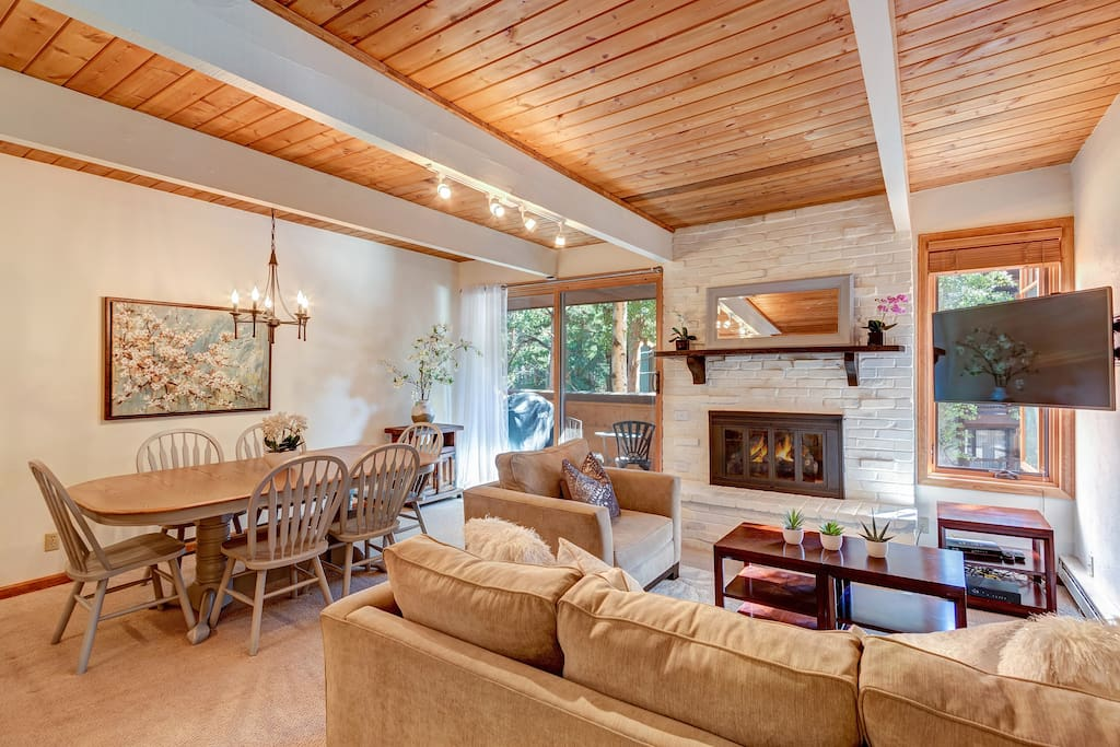 Open concept living area with Crate & Barrel sleeper sofa, wood burning fireplace and a flat screen TV