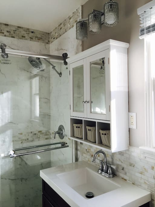Newley remodeled Marble bathroom with large a large shower head, tempered glass shower doors & TOTO toilet.