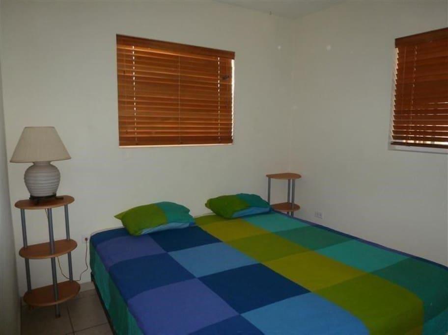 Masterbedroom aan achterzijde grenzend aan tropische tuin en voorzien van 2-persoonsbed, airconditioning en voldoende opbergruimte