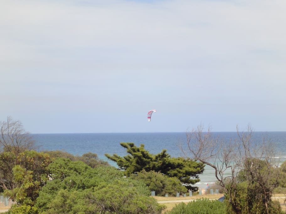 BALCONY VIEW. This is the view as kite boarders and wind surfers sail past the beachfront balcony.