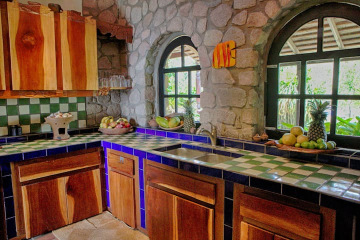 The vibrant kitchen is handmade utilizing local woods and stone.
