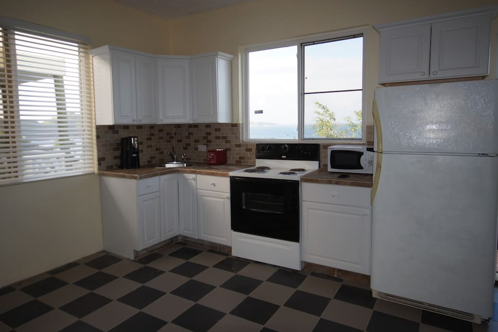 Kitchen with coffee maker, microwave and toaster. Blender in cabinet, fully equipped with pots, pans, utensils, etc.