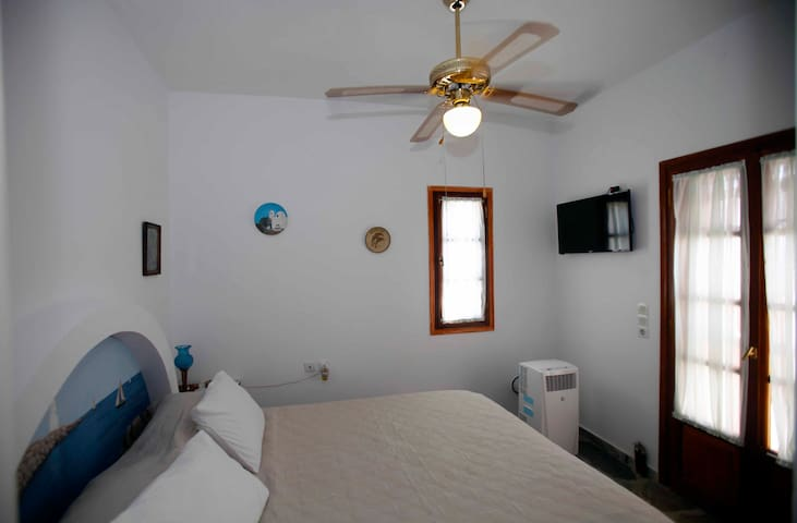 Master bedroom with a California King size bed, air conditioning, television and access to second floor balcony.