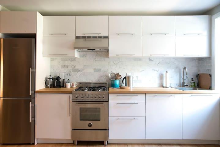 Kitchen with Nespresso machine, Italian stove, dishwasher and electric kettle.
