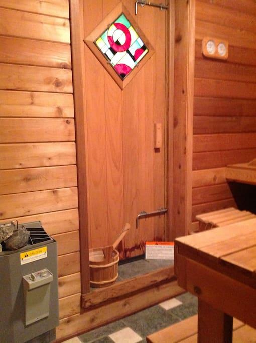 Finnish (dry heat) sauna with natural cedar walls, doors, & benches & tile floor