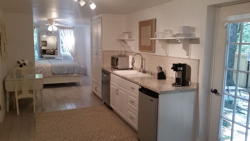 Kitchen with dishwasher, refrigerator, microwave and hot plate.