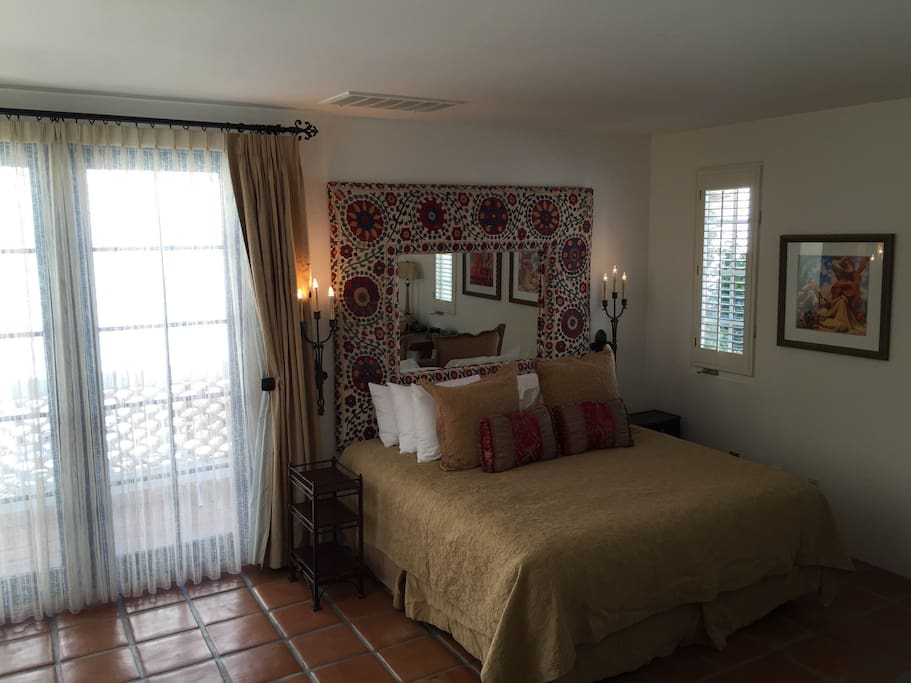 Bedroom with king bed and Spanish furnishings. Saltillo tile and mountain/pool views throughout.