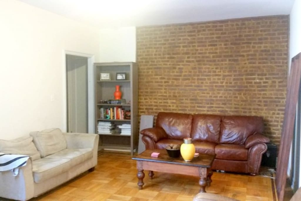 Large Living room with Flat screen tv, couch, love seat and armchair.