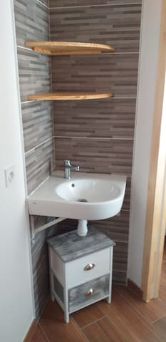 Salle de bain équipée d'un bac à douche, d'un lavabo d'angle , wc suspendu et sè-che serviettes, petit meuble de rangement prise électrique 230v, vmc,  petite fenêtre, porte à galandage ouvrant sur la chambre à coucher .