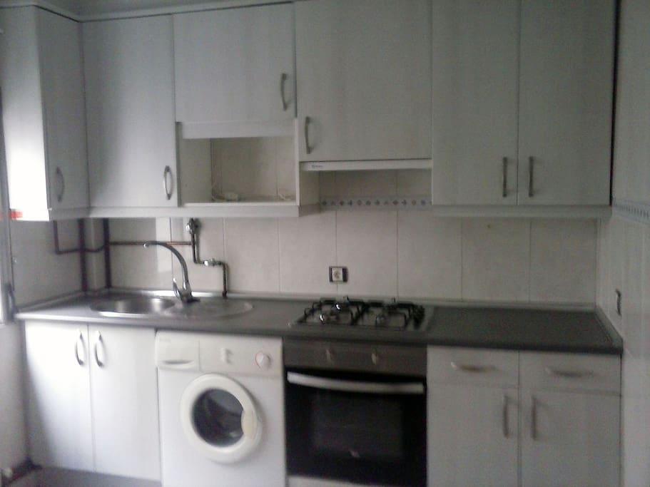 La cocina cuenta con lavadora, 4 fuegos, horno eléctrico y frigorífico.
