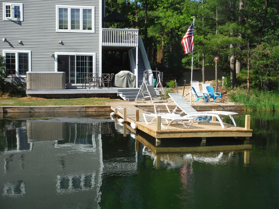 Dock to deck over looking lake with 2 lawn chairs
