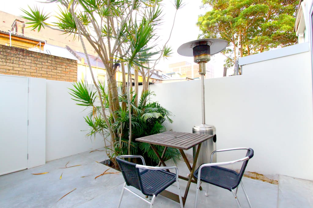 The backyard complete with a gas space heater and a breakfast table.