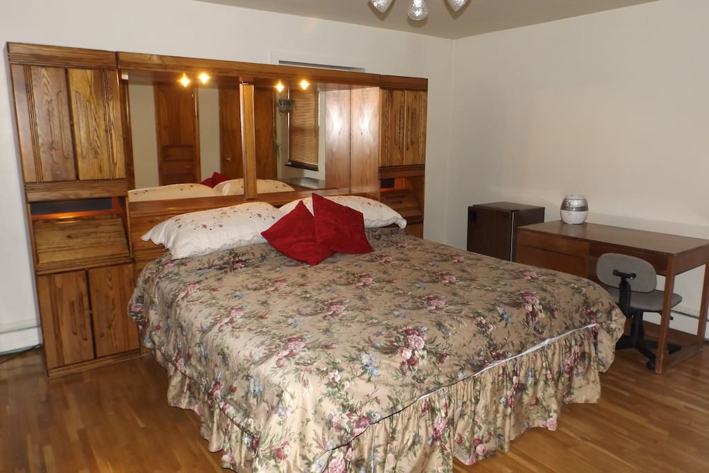 Spacious room, king size bed with hardwood floors , 3 1/2 closets, desk, refrigerator, ceiling fan and view of back yard.