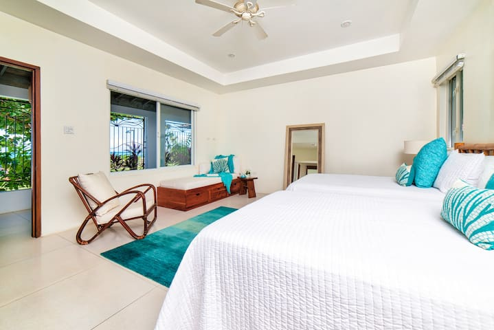 Bedroom #4      16x18 feet Two Double beds and a sofa bed, en suite bathroom, a/c, ceiling fan, garden, pool, and turquoise Caribbean Sea views