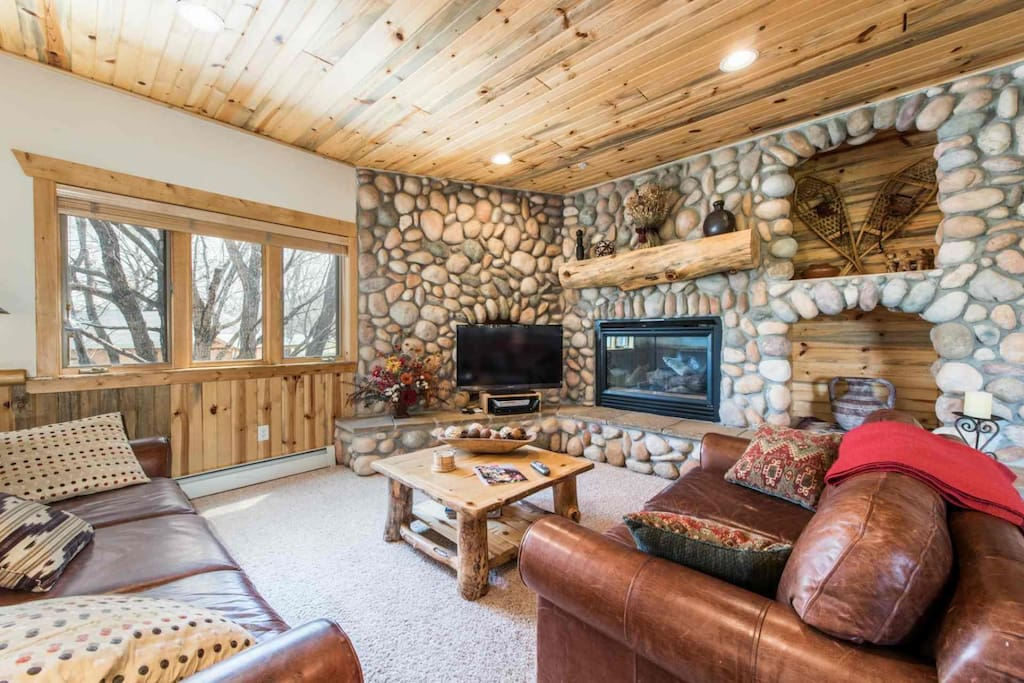 The living room is equipped with a large HDTV, comfortable leather sofa and matching loveseat, gas fireplace and river rock detailing.