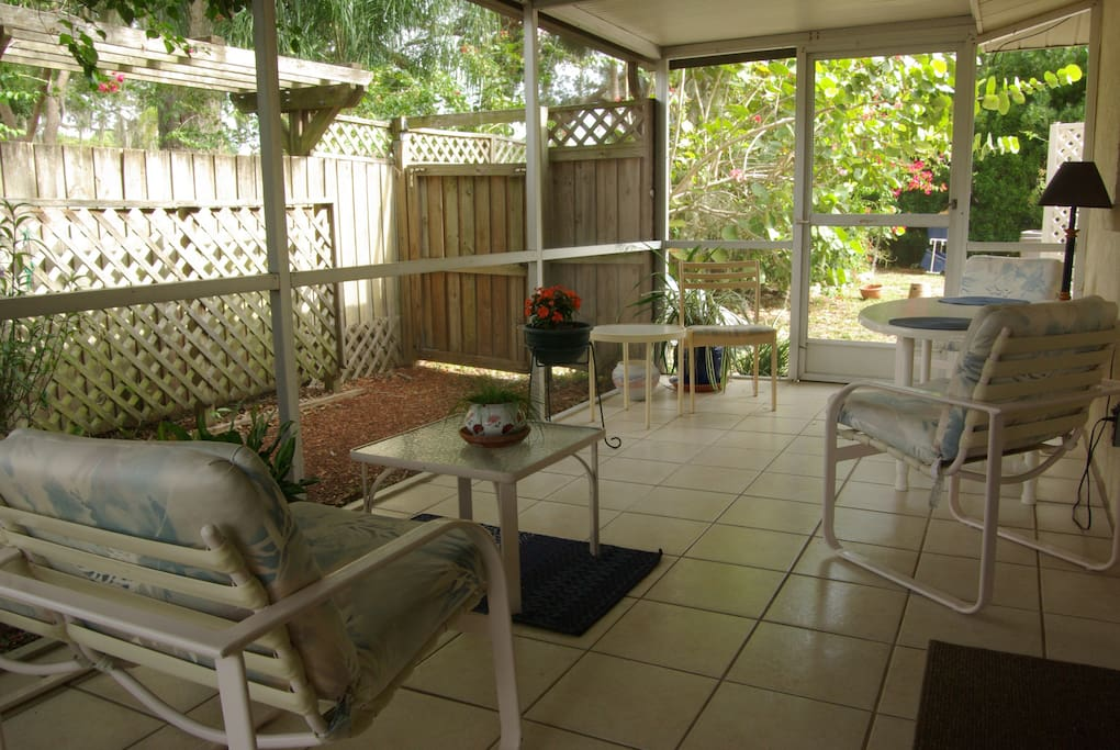 Tiled screen porch for relaxing or casual dining.