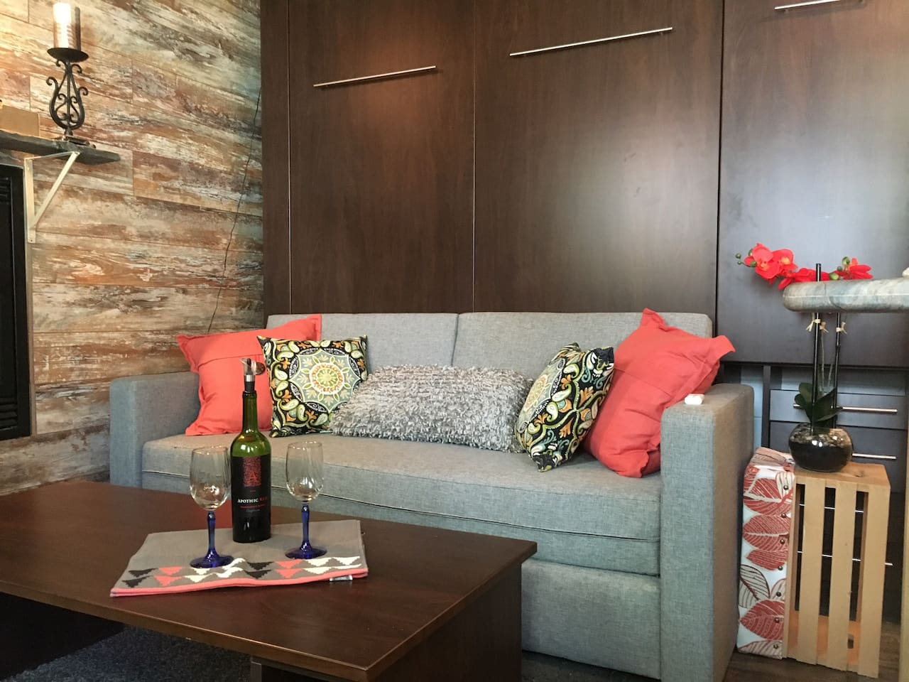 The living space includes a comfortable couch and coffee table, perfect for a romantic evening by the fireplace or quiet movie night with Smart TV.