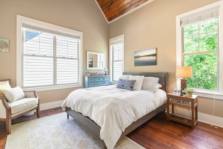 This upstairs queen bedroom sits right off the kitchen. More beautiful vaulted  ceilings! An adjoining full bath is located right outside the bedroom door.