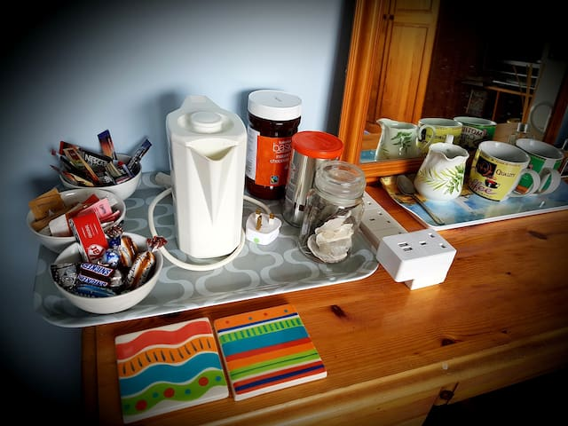 Tea/coffee/chocolate making facilities in the room with chocs and a biscuit.