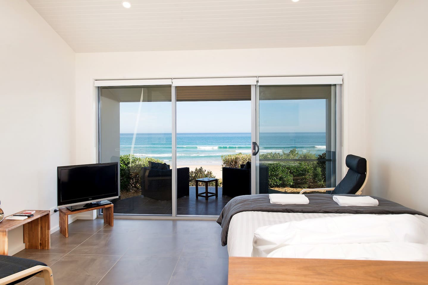 View of beach from bed, with two armchairs inside and patio setting