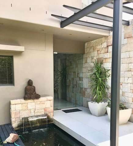 Inviting entrance to home with fish pond